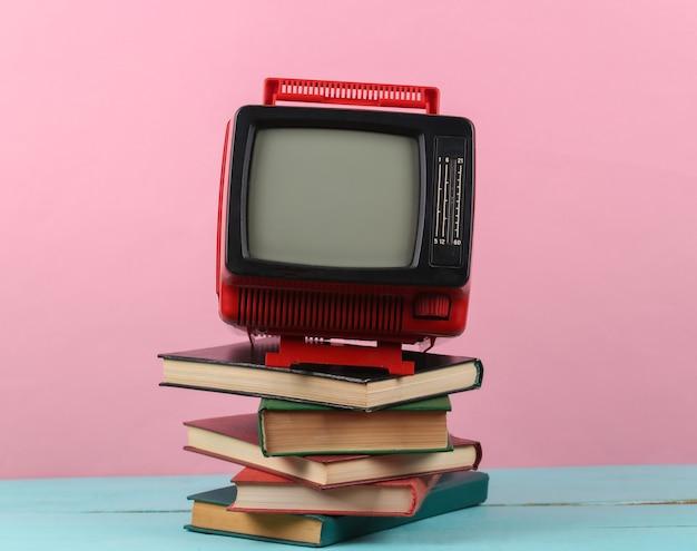 Tv rétro et pile de livres sur fond rose. enseignement à distance à la télévision.