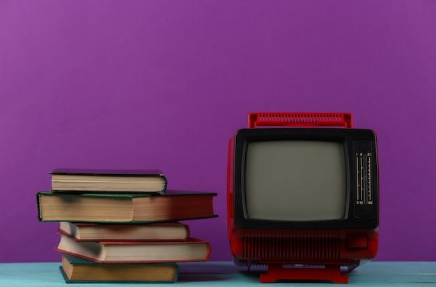 Tv rétro et pile de livres sur fond violet. enseignement à distance à la télévision.