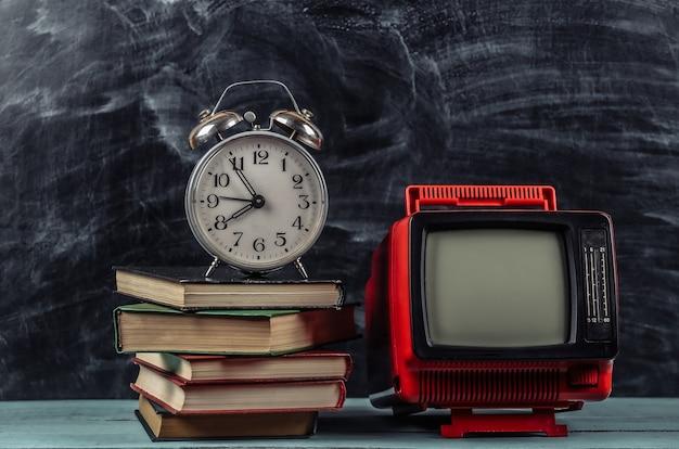 Tv rétro et pile de livres avec réveil sur fond de tableau noir. enseignement à distance à la télévision.