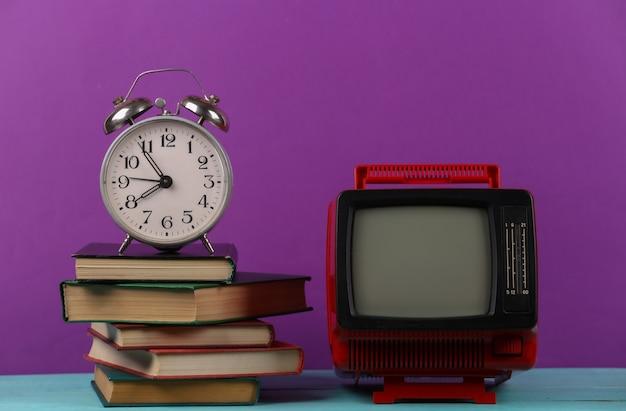 Tv rétro et pile de livres avec réveil sur fond violet. enseignement à distance à la télévision.