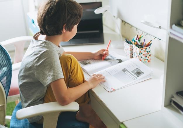 Tween boy do devoirs apprendre l'écriture d'une langue étrangère dans le livre de l'élève avec un ordinateur portable ouvert à la salle de l'enseignement de la dictée à domicile