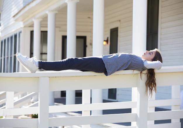 Tween kid fille ayant se détendre dans la clôture du parc