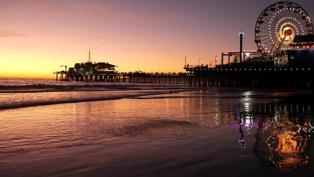 Twilight pier, grande roue illuminée, santa monica ocean beach, californie, los angeles, usa.