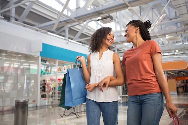 Two laughing black girls walking in shopping mall