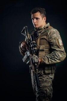 Un type brutal dans des combinaisons d'airsoft militaires pose avec une arme dans ses mains sur un fond foncé