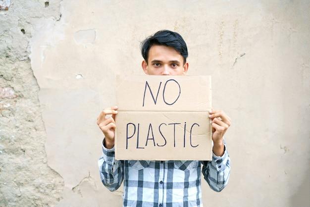 Type caucasien tenant l'inscription aucun concept de protection de l'environnement en plastique de la pollution des ordures ...