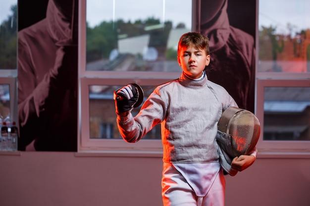 Un type en costume d'escrime avec une épée à la main, néon. un jeune modèle s'entraîne et s'entraîne en mouvement, en action. sports, jeunesse, mode de vie sain.
