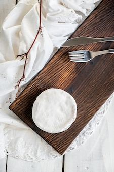 Type de fromage brie. le camembert. fromage brie frais et une tranche sur une planche de bois. italien