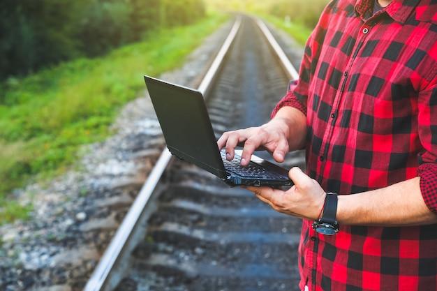 Un type avec un ordinateur portable est assis sur la voie ferrée. travailleur hipster indépendant. l'homme travaille en voyageant.