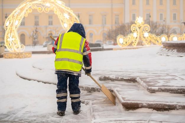 Le type de service municipal nettoie la neige des rues avec la pelle b
