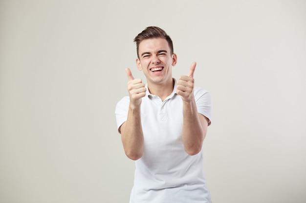 Un type vêtu d'un t-shirt blanc et d'un jean rit et lève le pouce