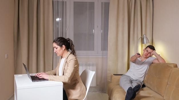 Types de brune concentrés sur un ordinateur portable gris assis sur une chaise à table et un gars qui s'ennuie appuie sur les boutons de la télécommande du téléviseur allongé sur un canapé à l'isolement