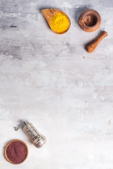 Types d'épices de différentes moutures dans un bol en bois avec une ponceuse sur pierre, poser à plat
