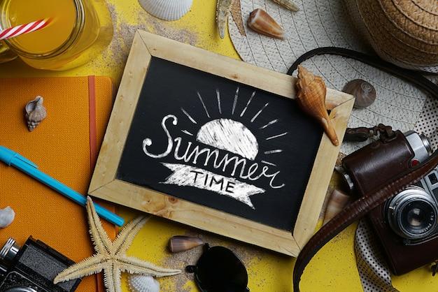 Typographie de l'heure d'été sur tableau noir entre les accessoires de plage d'été