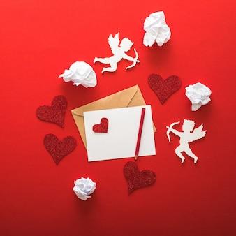 Typographie de voeux joyeux saint valentin avec des éléments de la saint-valentin de lettre, cadeaux, coeurs sur fond de papier rouge.