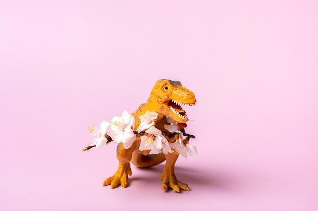 Tyrannosaurus dinosaure jouet tenant une fleur d'abricot dans ses pattes