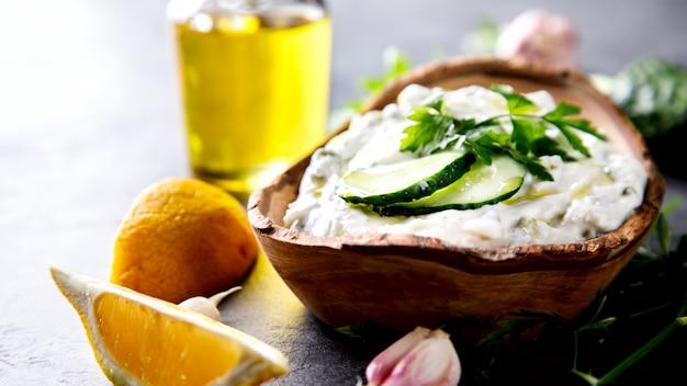 Tzatziki sauce grecque traditionnelle avec des ingrédients concombre, ail, persil, citron, menthe.