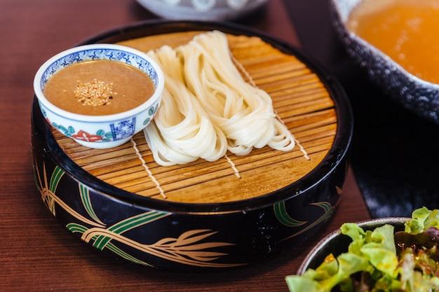 Udon frais avec sauce au sésame servi dans une natte de bambou avec une salade.