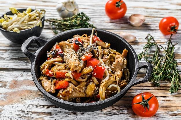 Udon sauté de nouilles au poulet et aux légumes dans une casserole sur blanc. vue de dessus