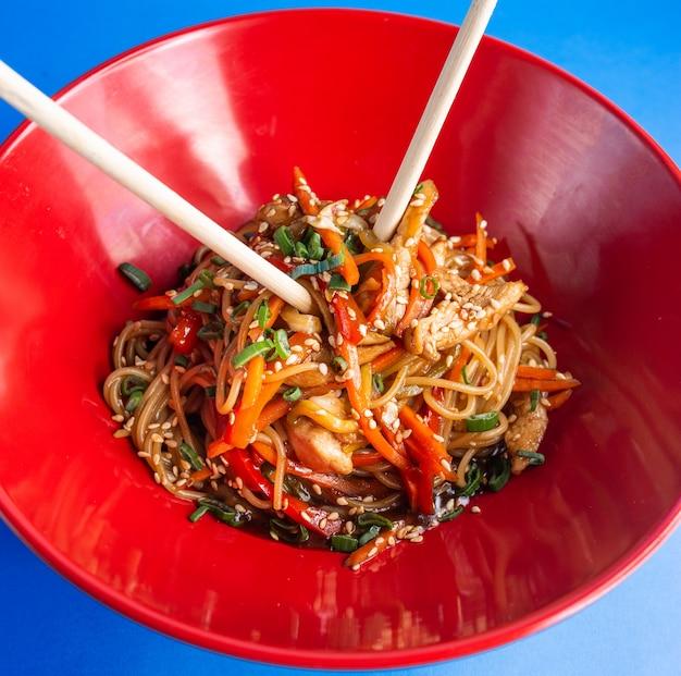 Udon sauté de nouilles au poulet, poivron, carotte, oignon de printemps, sauce soja et sésame dans un bol