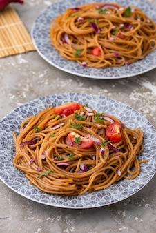 Udon sauté nouilles avec des légumes dans l'assiette avec des baguettes