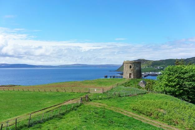 Uig tower ou captain fraser's folly affichage du port d'uig en arrière-plan en été , île de skye , ecosse