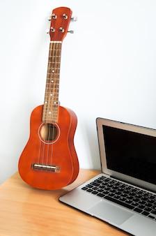 Ukulélé guitare à quatre cordes hawaïenne sur table en bois et ordinateur portable.