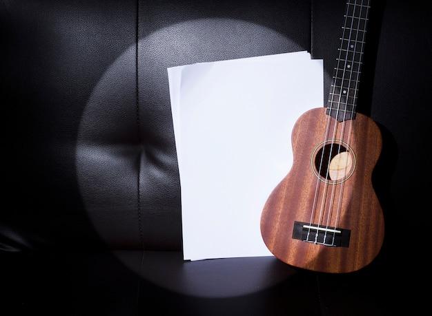 Ukulele in sport light et notes de papier de musique vierges.