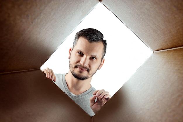 Unboxing, un homme ouvre la boîte et regarde à l'intérieur