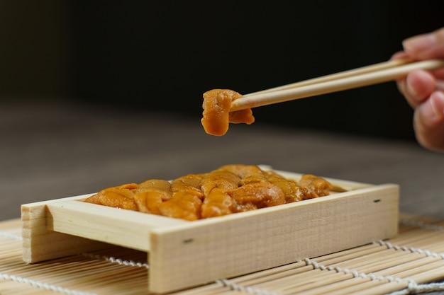 Uni sushi en baguettes. oursin (uni sashimi), cuisine japonaise.