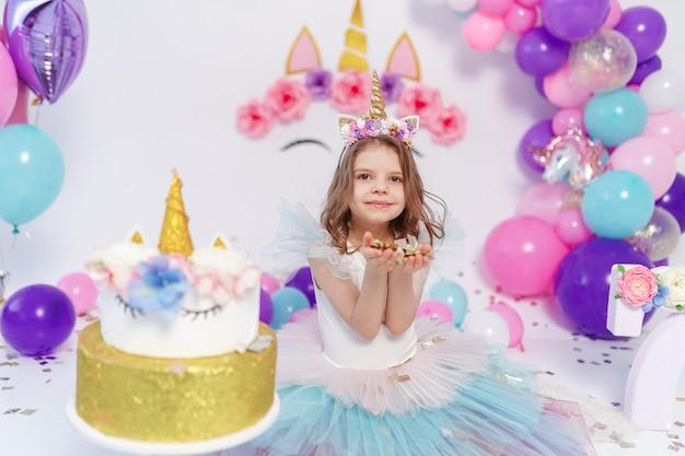 Unicorn girl jette des confettis. idée pour décorer une fête d'anniversaire de style licorne. décoration de licorne pour fille de fête