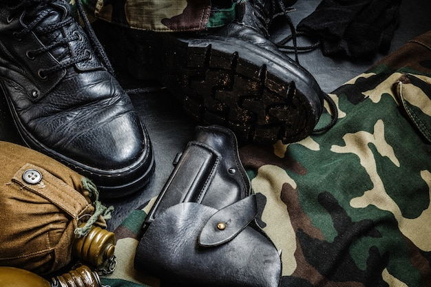 Uniforme de camouflage militaire et des bottes. un ensemble d'éléments de pistolet de flasque militaire sur un fond sombre