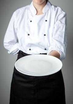 Uniforme de chef avec assiette vide blanche bienvenue promotion de restaurant plat présent