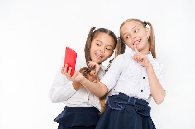 L'uniforme scolaire des filles prend un smartphone selfie. posant pour prendre une photo parfaite. loisirs de fille. les filles veulent juste s'amuser. la coiffure mignonne des écolières utilise un téléphone portable ou un smartphone pour partager des photos.