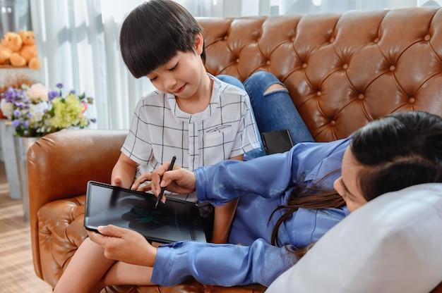 Unité familiale asiatique à la maison. maman enseigne à un enfant pour l'apprentissage en ligne. nouveau mode de vie normal.