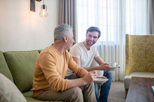 Unité. père et fils assis l'un à côté de l'autre et buvant du thé