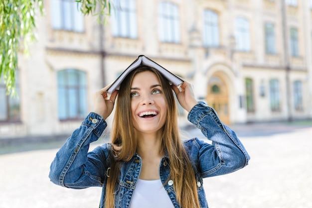 Les universitaires bourses d'études émotion funky drôle expression faciale facile excellente bonne note concept gros plan photo portrait de mignon assez fou attrayant avec personne aux cheveux longs tenant un livre sur la tête