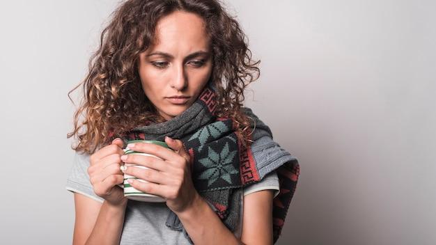 Unwell jeune femme avec un foulard autour du cou tenant une tasse de café