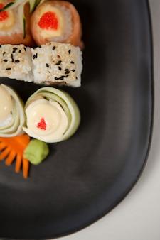 Uramaki et nigiri sushi servi dans une plaque noire sur fond blanc