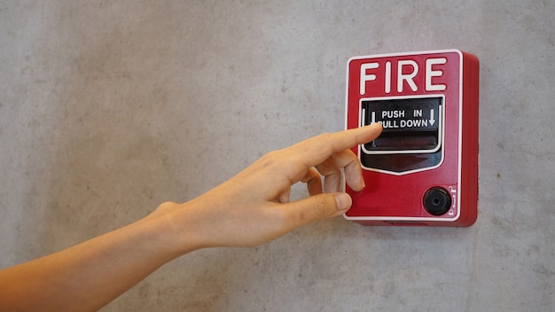 Urgence d'alarme incendie ou équipement d'alerte ou d'avertissement de cloche de couleur rouge avec la main dans le bâtiment pour la sécurité.