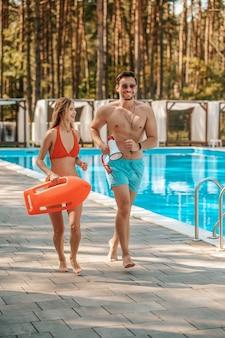 Urgence. deux sauveteurs de la piscine courant vers le lieu d'urgence