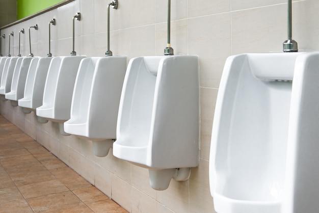 Urinoir blanc dans la salle de bain des hommes.