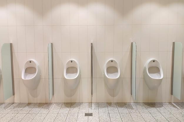 Urinoirs blancs dans la chambre des hommes sur la vue de face du mur