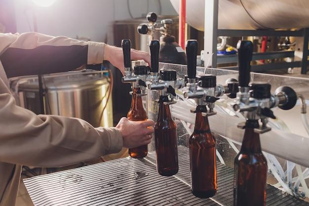 Usine de brasserie renversant de la bière dans des bouteilles en verre sur des lignes de convoyage. travail industriel, production automatisée d'aliments et de boissons. travail technologique à l'usine.