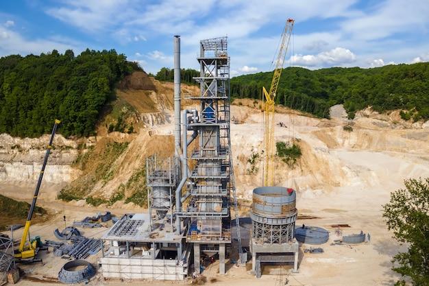 Usine de ciment à l'exploitation à ciel ouvert de matériaux de construction en pierre de sable avec des excavatrices et des camions à benne basculante.