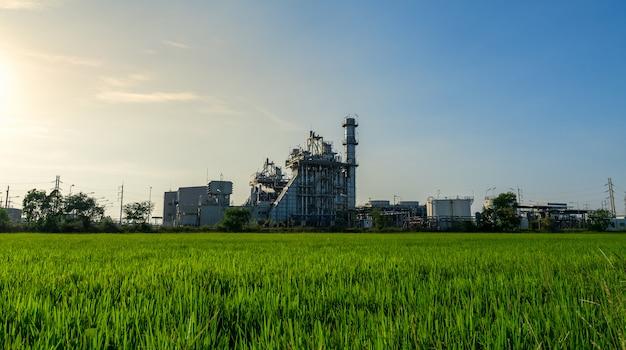 Usine d'industrie de raffinerie de pétrole et de gaz. sous ciel nuageux avec prairie verte