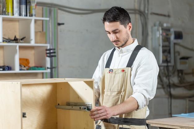 Usine de meubles, petites entreprises et concept de personnes - jeune travailleur travaille dans une usine