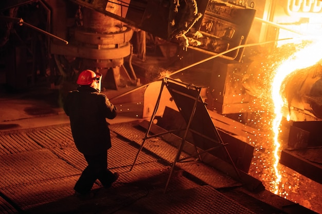 Usine de production d'acier. un four de fusion électrique. un ouvrier d'usine prélève un échantillon de métal.