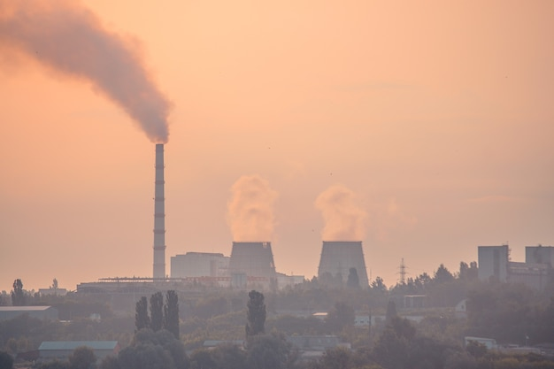 Usine de silhouette avec de grandes cheminées dans le smog