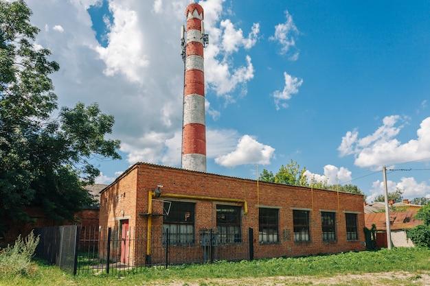Usine ou usine abandonnée en briques rouges avec haut tuyau d'échappement